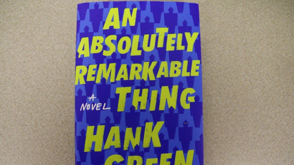"""""""An Absolutely Remarkable Thing"""" is written by Hank Green. The book tells the story of art school graduate April May, who rockets to internet stardom after posting a YouTube video about the sudden appearance of a human-like statue in New York City."""