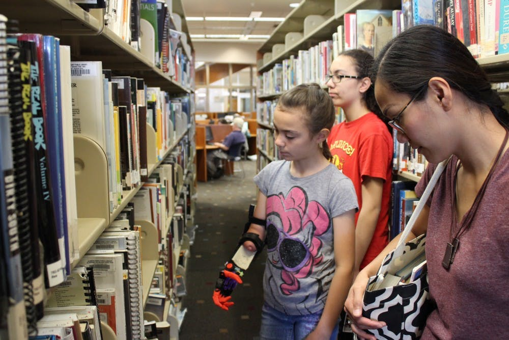 Violet Hall looks at music books with her mother, Milet Hall, and older sister at the Monroe County Public Library. Violet just started playing the violin with the help of her 3D printed arm, which was designed by an IU lecturer.