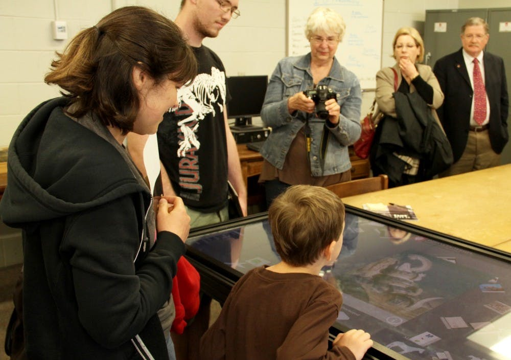 Visitors try out the visual interactive information about different kinds of fossils during the IU Paleontology event Saturday at Geology building.
