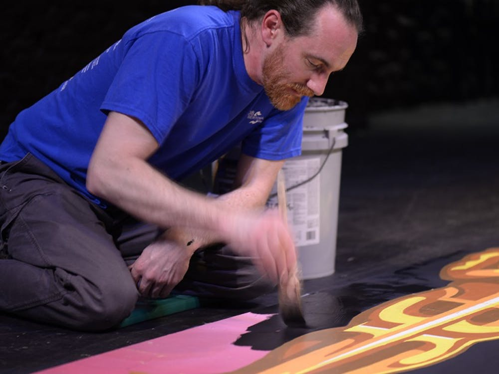 David DeSante paints the Oscar statue onto planks to use as props during an Oscar weekend event at the Buskirk-Chumley Theater. DeSante recently began working as the theater's technical director.