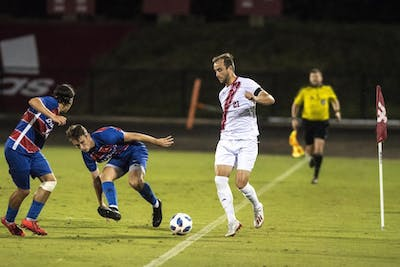 Redshirt junior Spencer Glass dribbles past a pair of DePaul defenders Aug. 24 at Bill Armstrong Stadium. Last weekend the No. 4 IU men's soccer squad battled against Seattle University.
