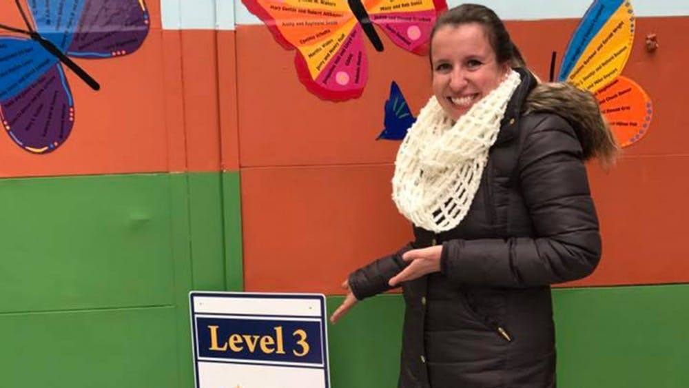 Childcare Coordinator Marcella Ettinger displays the level 3 achievement outside the daycare, in the courtyard at Middle Way House.