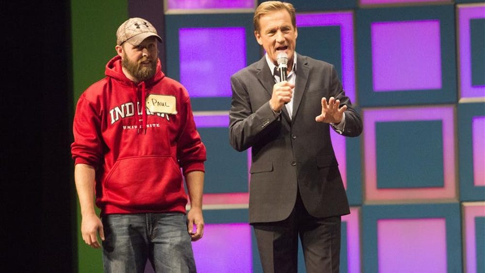 Contestant Paul Brown and host Patt Finn discuss the rules of the game on Thursday at the IU Auditorium. Brown was the first contestant to make it to the stage.