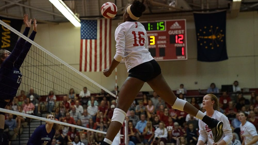 Junior middle blocker Deyshia Lofton spikes the ball against a Northwestern defender Sept. 21 in University Gym. IU is 2-2 in Big Ten Conference play.