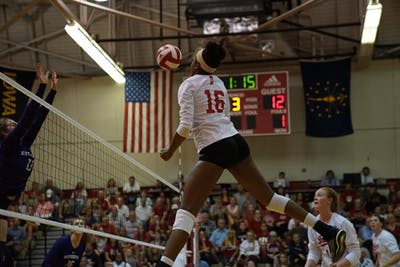 Junior middle blocker Deyshia Lofton spikes the ball against a Northwestern defender Sept. 21 in University Gym. IU won 3-1 against the Wildcats.