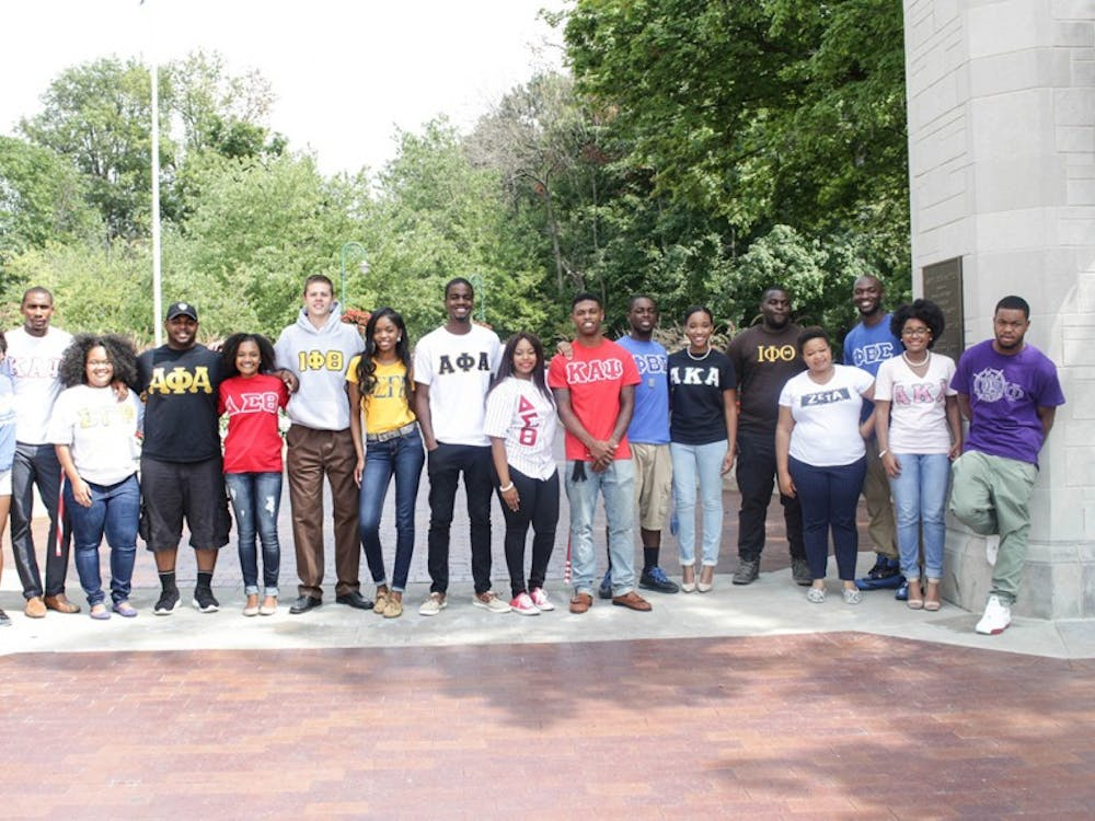 """Representatives from the nine historically black fraternities and sororities at IU pose for a photo by Sample Gates. A permanent row of limestone markers will have the names of the United States'nine original black greek chapters — known as the """"Divine Nine"""" —arranged in an arc along the sidewalk that leads to the entrance of the Neal-Marshall Black Culture Center building."""