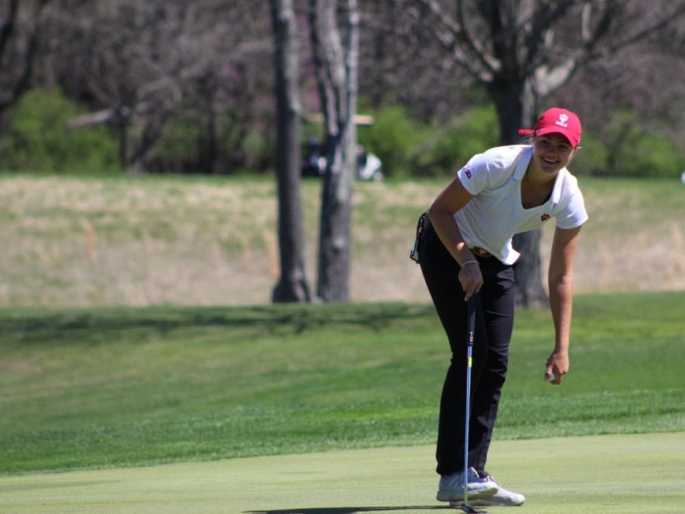 Freshman Emma Fisher picks her ball out of the hole after sinking a putt Saturday, April 8, 2017, during the IU Invitational at the IU Golf Course. The IU women's golf team will take part in the Alexa Stirling Women's Intercollegiate this weekend.