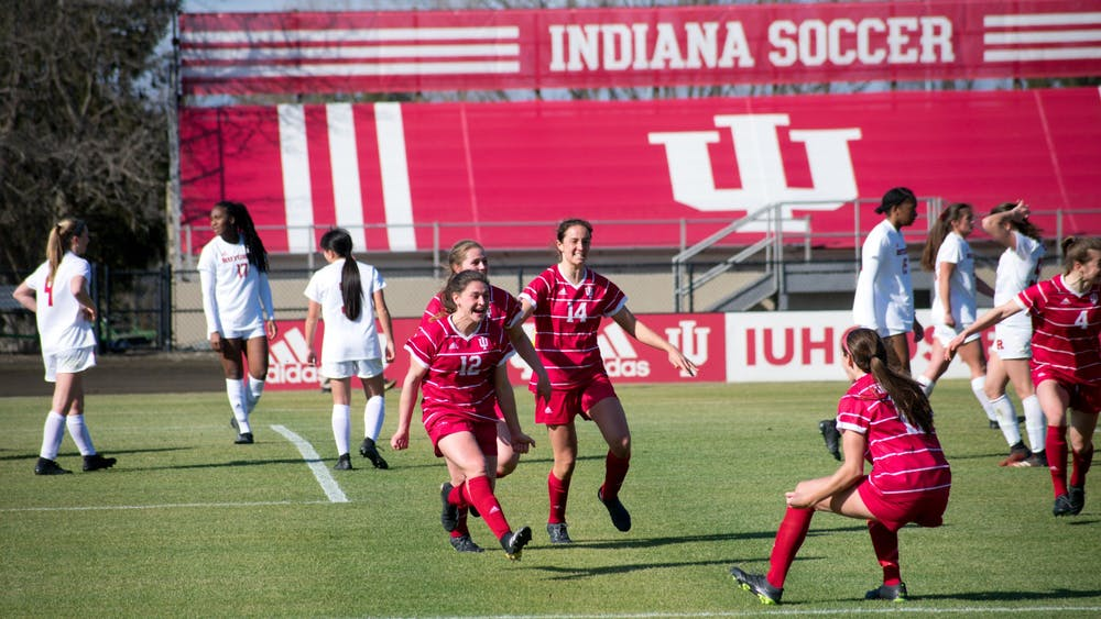 Players on the IU women's soccer team celebrate Feb. 25 during the game against Rutgers. The No. 24 Hoosiers won against the Maryland Terrapins 3-2 Sunday.