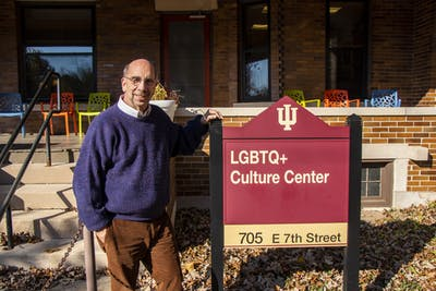 Doug Bauder stands by the sign in front of the LGBTQ+ Culture Center. Bauder is retiring after 25 years as the founding director of the LGBTQ+ Culture Center.