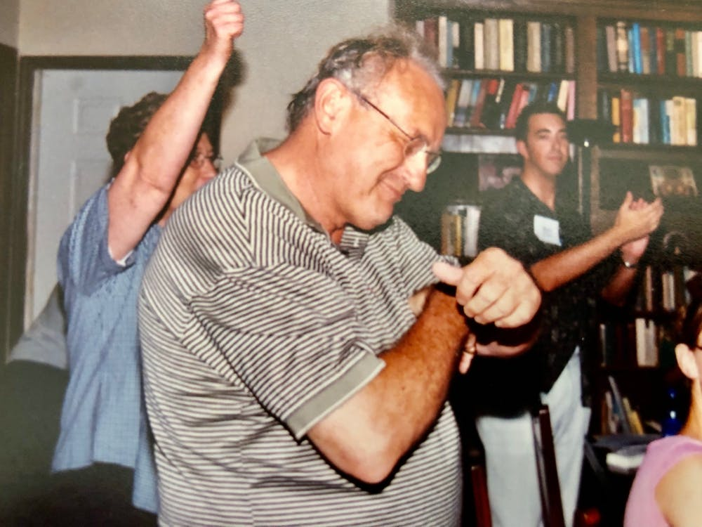 Carl Ziegler dances at his house with Mark Helmsing and other students after a back-to-school student dinner in August 2003. Ziegler, 80, died on April 19.