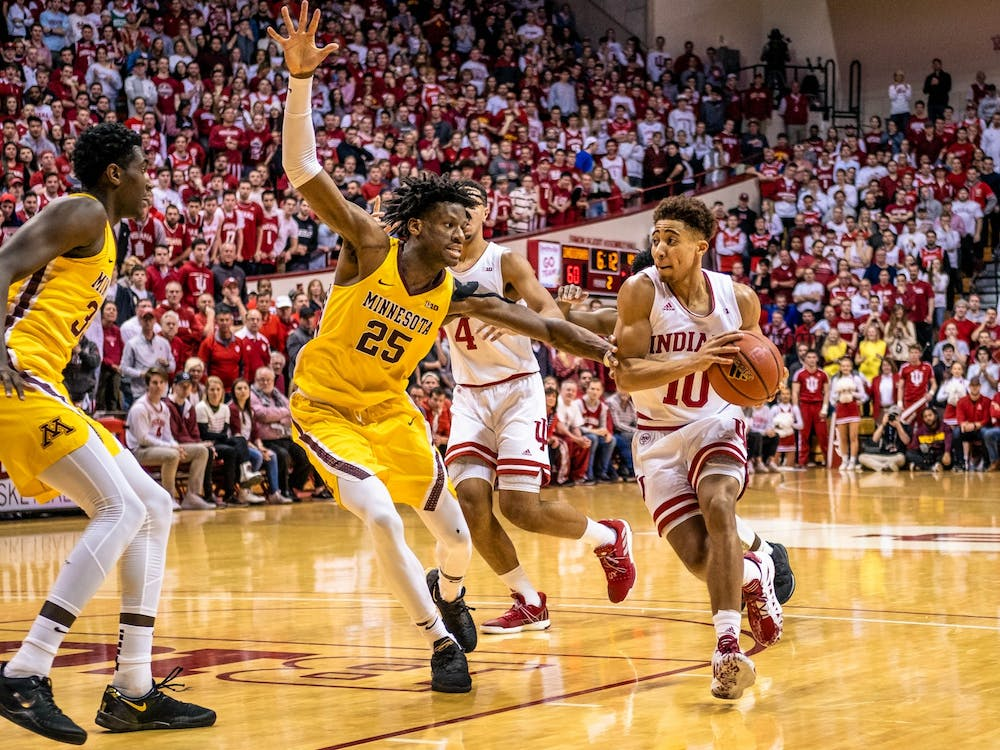 Sophomore guard Rob Phinisee dribbles past Minnesota sophomore center Daniel Oturu to make a layup March 4 in Simon Skjodt Assembly Hall. IU will play Wisconsin on Saturday in Bloomington.