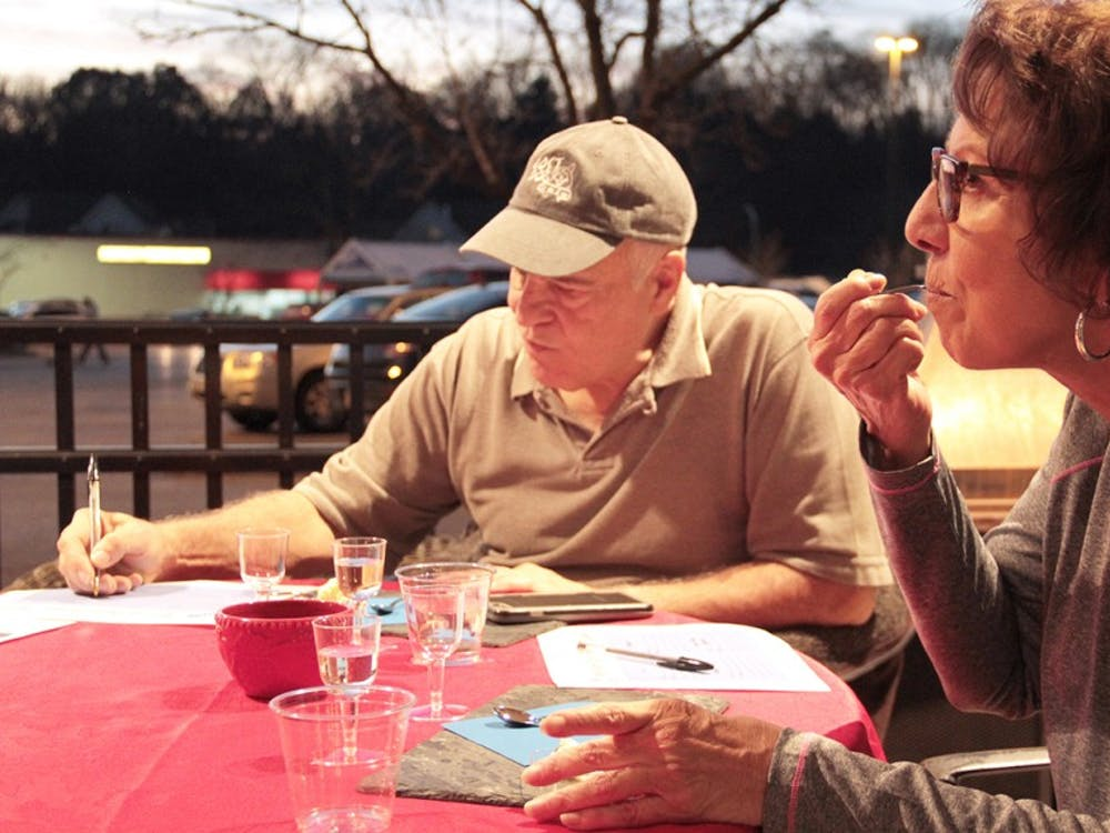 Charles Beckett (left) and Janis DeStefano taste  wine and cheese provided by Kroger on Thursday evening.