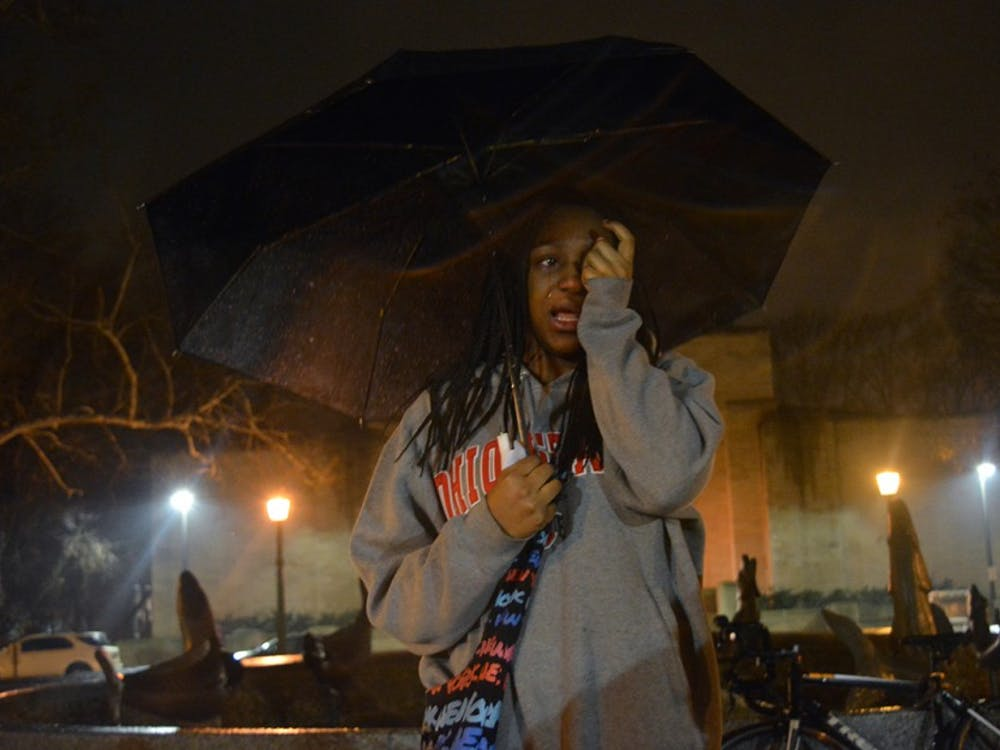 Freshman Alese Allen cries as she recalls fond memories of Djiby. Students gathered at Showalter Fountain to tell others how the c-store worker changed their lives.