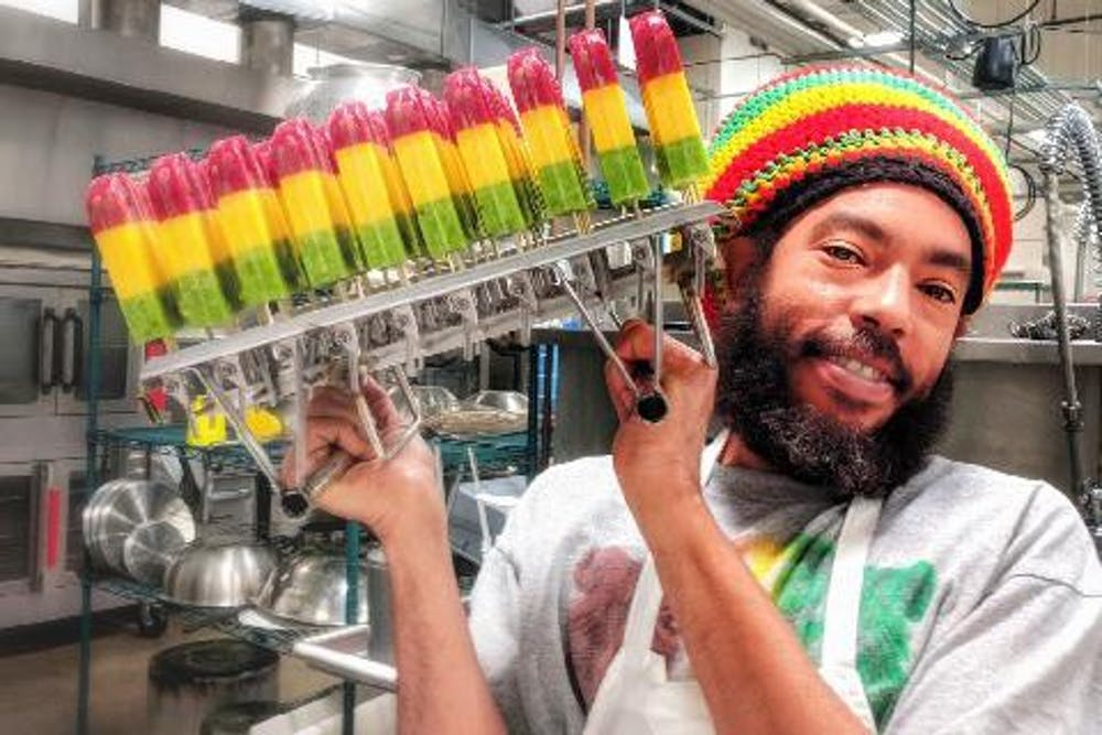 <p>Iuri Santos, owner of the Rasta Pops cart, poses with some of his creations. Santos, a local businessman from Brazil, makes popsicles based on flavors in his home country.</p>