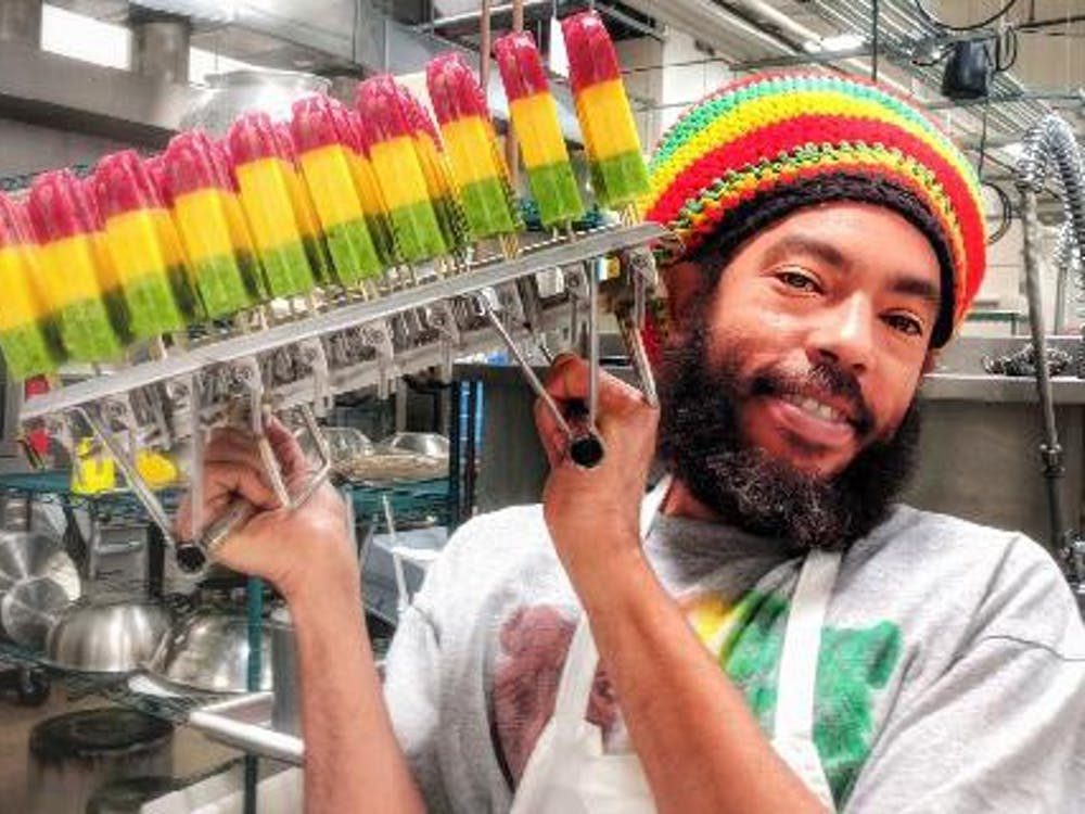 Iuri Santos, owner of the Rasta Pops cart, poses with some of his creations. Santos, a local businessman from Brazil, makes popsicles based on flavors in his home country.