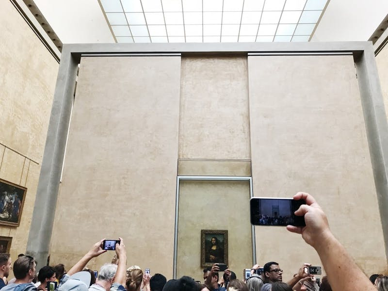 """Tourists take photos of """"Mona Lisa"""" at the Louvre Museum in Paris."""