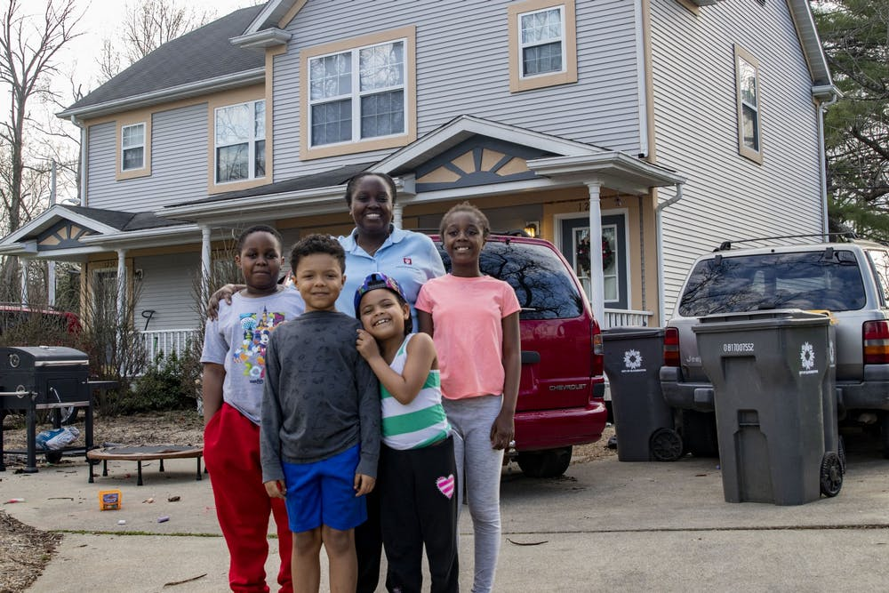 <p>IU Health registration specialist Eliza Carey stands with her children in front of her house March 30 in Bloomington. Carey decided to homeschool her children because of the coronavirus pandemic.</p>