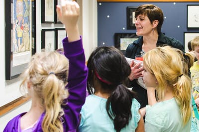 Lisa Champelli, children's strategist for the Monroe County Public Library, leads a group of second grade students in 2016 through the Maurice Sendak Exhibit at the library. The library's online summer reading program will be able to set up reading games and a reading minute system, according to Champelli.