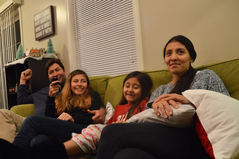 The Carmona family tries to settle on a television show in their living room in Bloomington. More than two years after fleeing violence in Venezuela, they await a decision over whether they will be granted asylum in the United States.