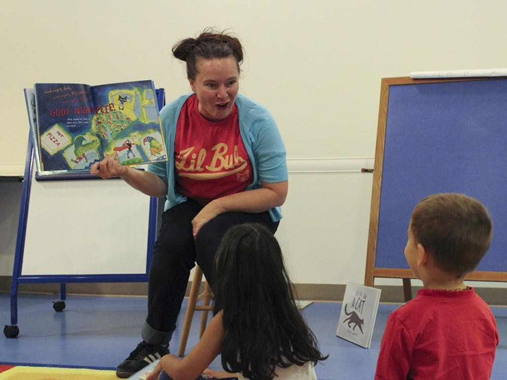 Abigal Mathai, 4 (left) and Ryan Moore, 3, (right) lsiten to the last story of the night from Christina Jones, community engagement librarian at Monroe County Public Library. Pajama Storytime is a frequent event, giving pre-school-aged children and their parents a relaxing evening.