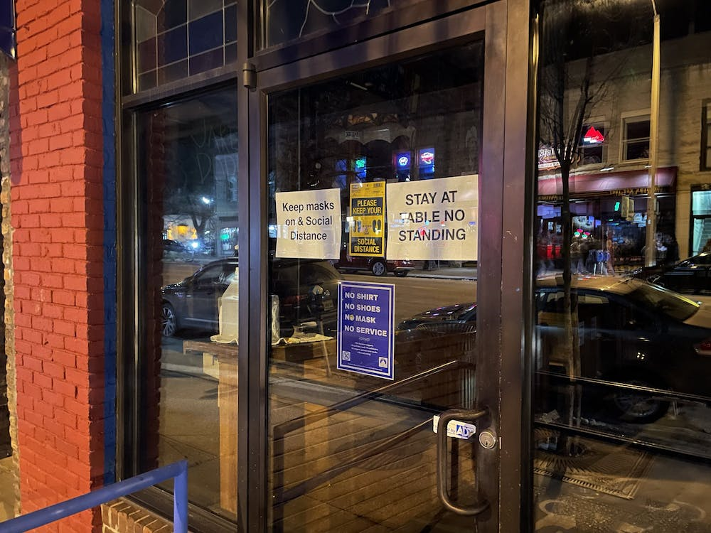 """The Bluebird's doors are closed with the lights off after the nightclub was temporarily shut down Feb. 26 to develop a COVID-19 safety plan. Following the shutdown, a new sign reading """"STAY AT TABLE NO STANDING"""" was added to the door."""