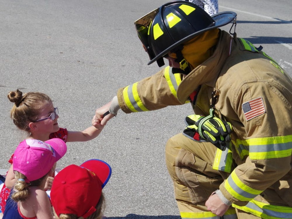 During the Bloomington Fourth of July Parade, a firefighter fist bumps with a little girl near the Monroe County Courthouse. The parade celebrating Independence Day involved around 90 different entries with hundreds of people lining the streets to watch.