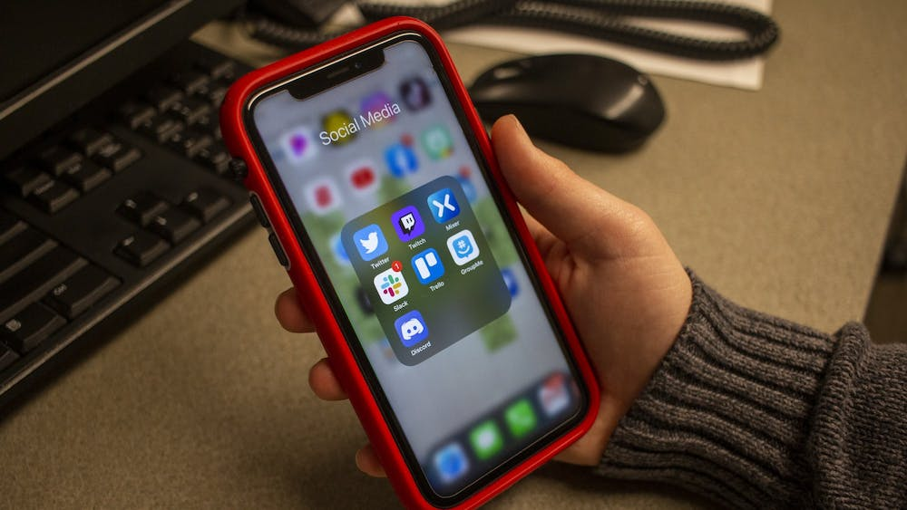 A students holds a phone showing his social media apps. Clearview AI's facial recognition software is used by hundreds of law enforcement agencies across the nation.
