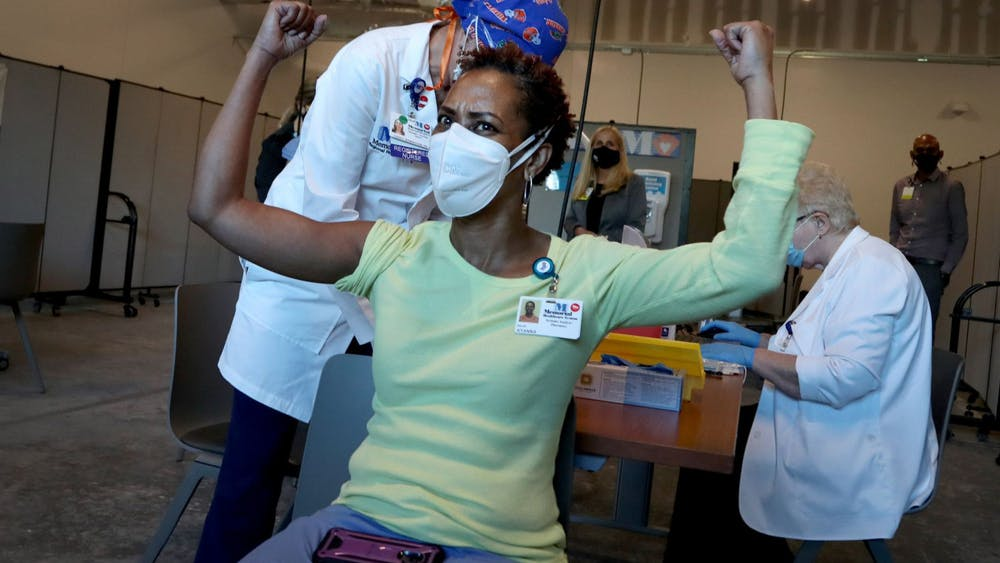 Ayanna Phillips, a Memorial Health systems analyst, celebrates after receiving the COVID-19 vaccine Monday in Miramar, Florida.