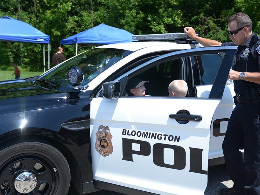 A Bloomington Police Department officer talks to Oliver and Isaiah Gough while they experience the front seat of a police car during the annual Touch a Truck event June 10, 2015. Wednesday's event will feature an array of fire trucks, ambulances, buses, bucket trucks and tractors.