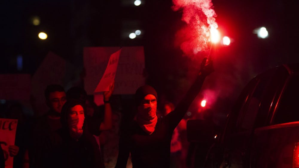 Some anti-facist, or antifa, protesters march down the street with red flares Sept. 7 to protest white supremacy in Bloomington. The group marched to Showers Commons, where the Bloomington Community Farmers' Market takes place.