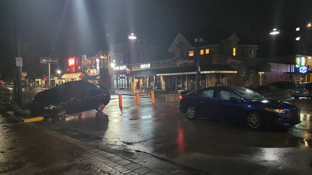 Cars sit in the street after being damaged by flood waters Friday night early on Kirkwood Ave. Emergency responders reported 17 water rescues, according to a release from the City of Bloomington on Saturday.