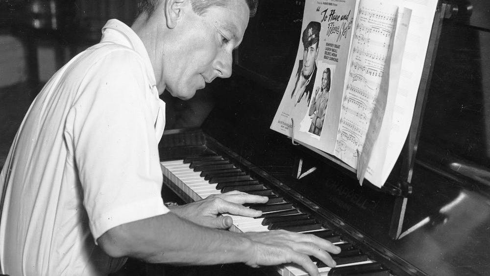 """Hoagy Carmichael plays the piano. Carmichael became famous after the popularity of his 1926 song """"Stardust."""""""