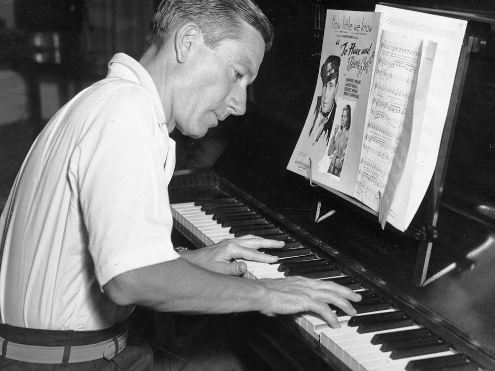 "Hoagy Carmichael plays the piano. Carmichael became famous after the popularity of his 1926 song ""Stardust."""
