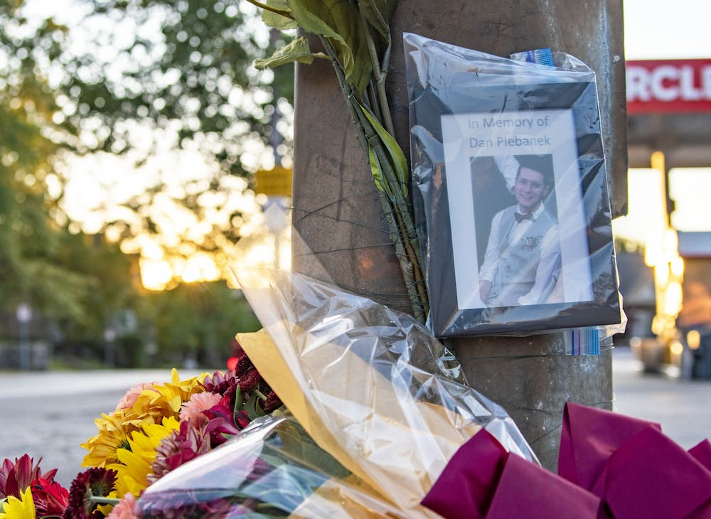 <p>The sun sets Oct. 1 behind a memorial to Daniel Plebanek at the corner of Third Street and Indiana Avenue. Dr. Plebanek was given a posthumous Ph.D. after he was killed in an accident last week.</p>