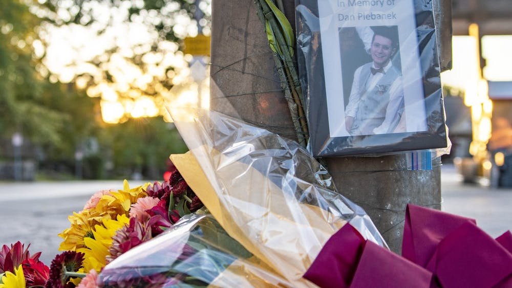The sun sets Oct. 1 behind a memorial to Daniel Plebanek at the corner of Third Street and Indiana Avenue. Dr. Plebanek was given a posthumous Ph.D. after he was killed in an accident last week.