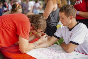 Freshman Trip Truman gets an arrow henna tattoo from artist Jeremy Stephens during CultureFest on Thursday evening at the Fine Arts Plaza.