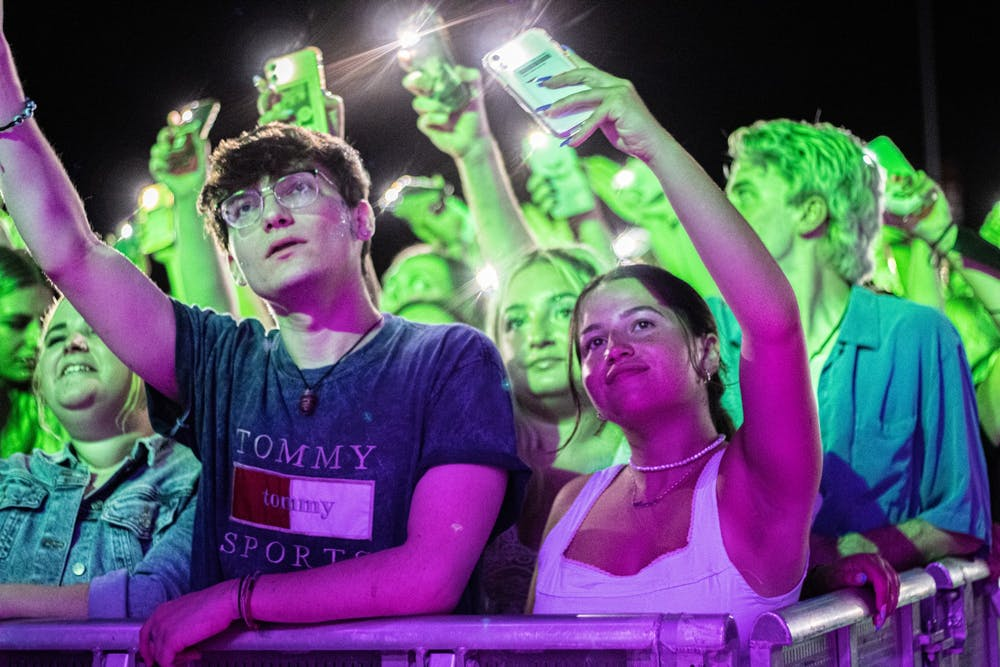 <p>Concertgoers wave their cellphones to the music Saturday night during the Indiana Memorial Union Board Block Party. </p>