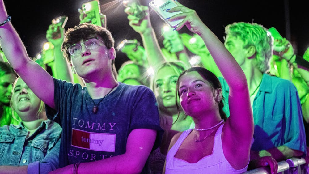 Concertgoers wave their cellphones to the music Saturday night during the Indiana Memorial Union Board Block Party.