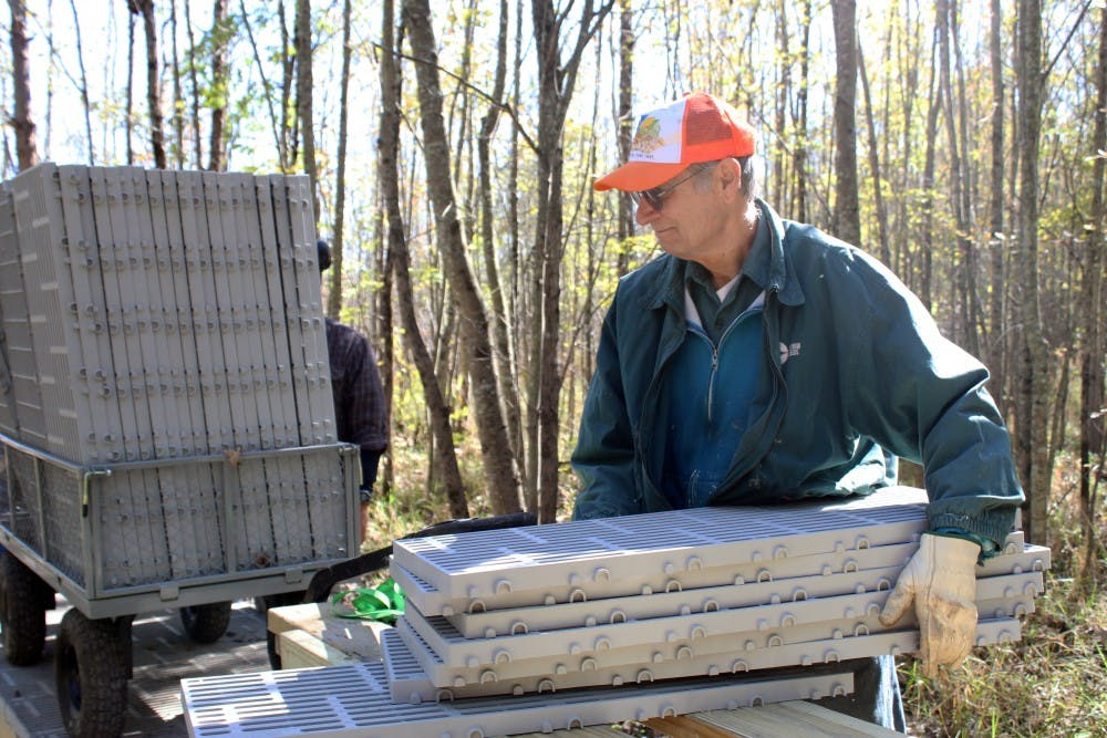 <p>Volunteer Tom Mayer gathers materials for the replacement of the boardwalk trail Oct. 18 at Beanblossom Bottoms Nature Preserve. The new boardwalk trail will be made of non-slip plastic materials.</p>