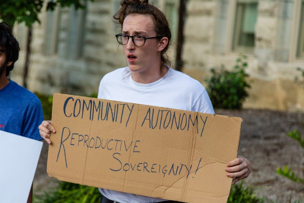 """<p>Junior Thomas Metcalf holds a sign which reads """"community autonomy, reproductive sovereignity!"""" before a rally against Supreme Court Justice Brett Kavanaugh on Oct. 10 near the Sample Gates.</p>"""