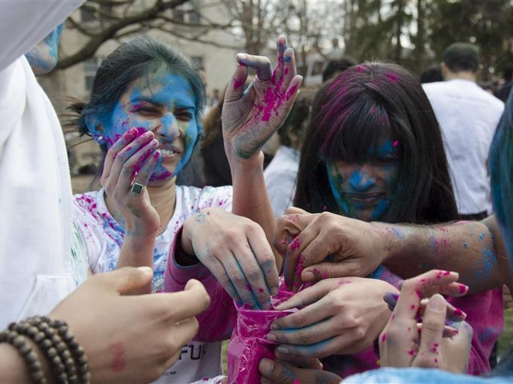 Students dig into a bag of pink paint powder during a Holi event on Wednesday evening at the Collins Living-Learning Center courtyard. Holi is a Hindu festival, where observers celebrate the beginning of spring by throwing multi-colored paint powder on one another.