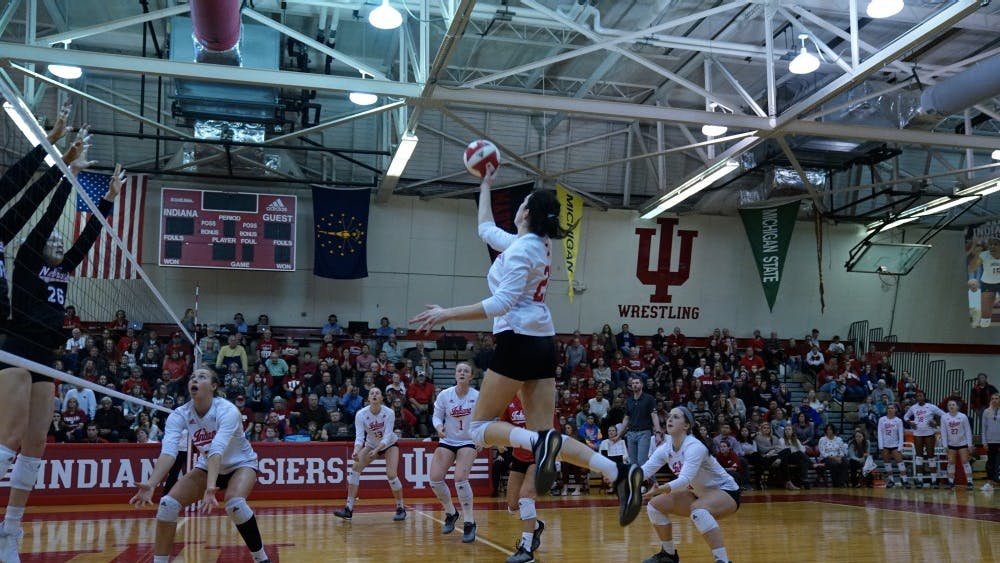 Sophomore outside hitter Kamryn Malloy floats the ball over the net against two Nebraska defenders Nov. 17 in University Gym. IU lost to Nebraska in straight sets, changing its season record to 16-13.