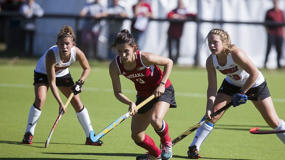 Senior midfielder Caitlin Bearish evades two Lousiville defenders on Sunday at the Field Hockey Complex. Indiana lost 2-0 in their final home game of the season.