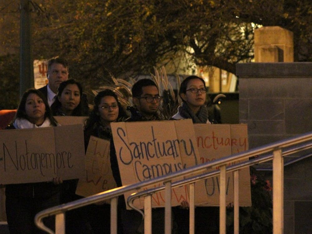 Students stand in the front row of the crowd holding signs. The crowd gathered in the Fine Arts Plaza on Thursday evening for a unity talk sponsored by IU administration and student organizations.