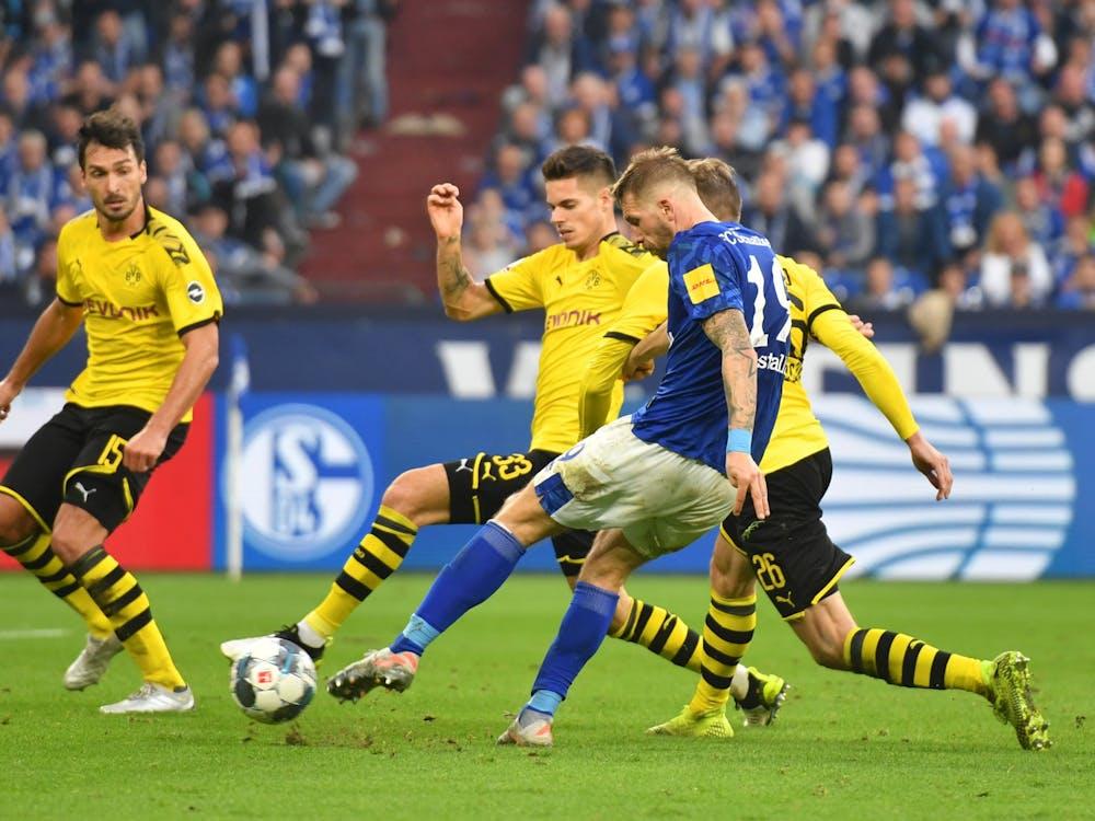 Guido Burgstaller, second from right, of Schalke, challenges the ball against Mats Hummels, Julian Weigl and Lukasz Piszczek, of Dortmund, during a match at Veltins-Arena in Gelsenkirchen, Germany.
