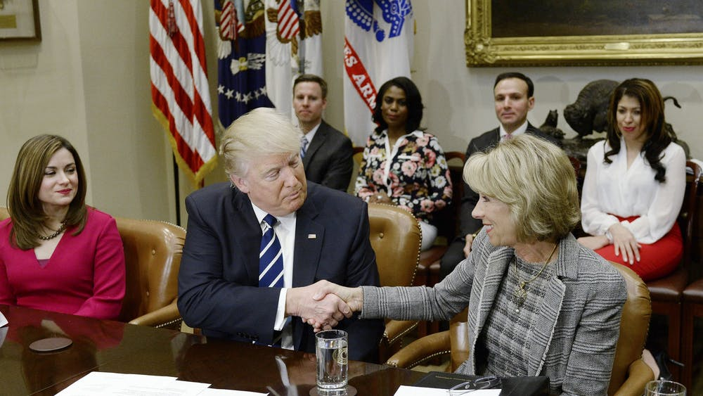 President Donald Trump shakes Education Secretary Betsy DeVos' hand during a parent-teacher conference listening session Feb. 14, 2017, in the Roosevelt Room of the White House in Washington, D.C.
