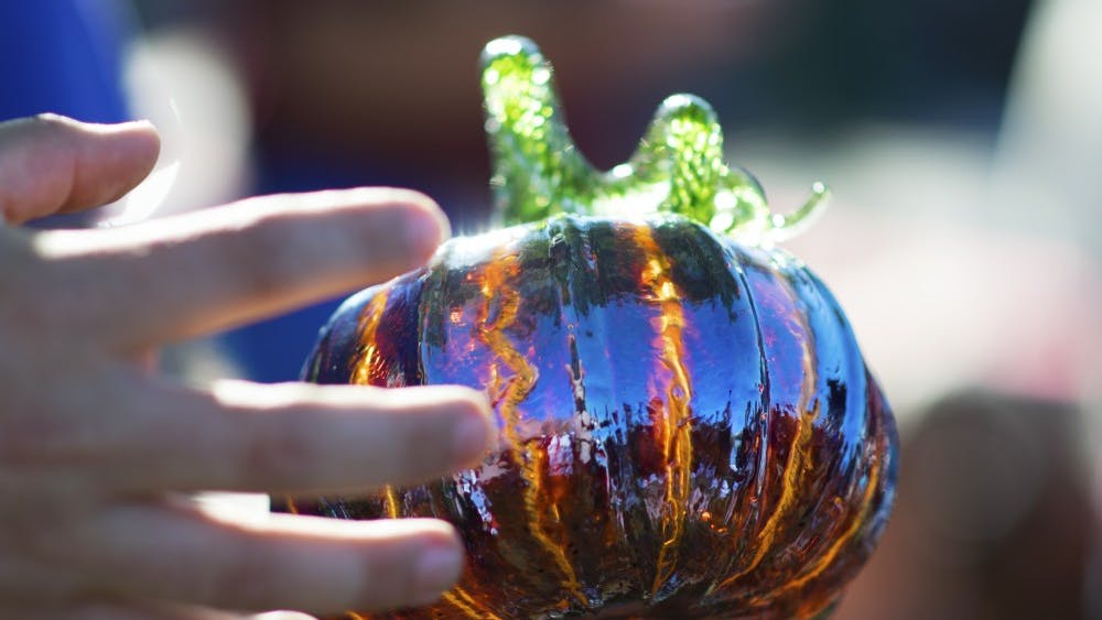 Tomas Gregg, a volunteer who has worked with the Bloomington Creative Glass Center for seven years, demonstrates how a crackle effect is achieved on some of the pumpkins at the Great Glass Pumpkin Patch on Saturday morning on the Monroe County Courthouse lawn. The crackle effect uses two layers of glass to create the two-tone effect.