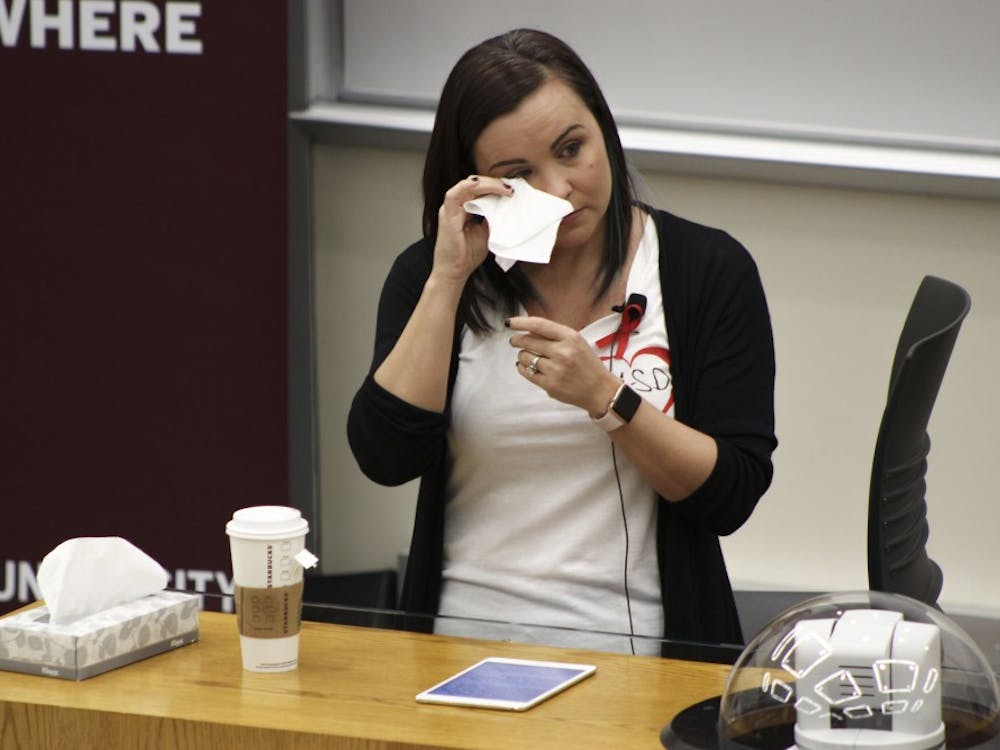 Katherine Posada, an IU alumna and a language arts teacher at Marjory Stoneman Douglas High School in Parkland, Florida, wipes her eyes while speaking to future educators on Friday in the School of Education. Posada talked about her experience in her school with the Feb. 14 shooting and the roles teachers have in stopping tragedies like this from happening.