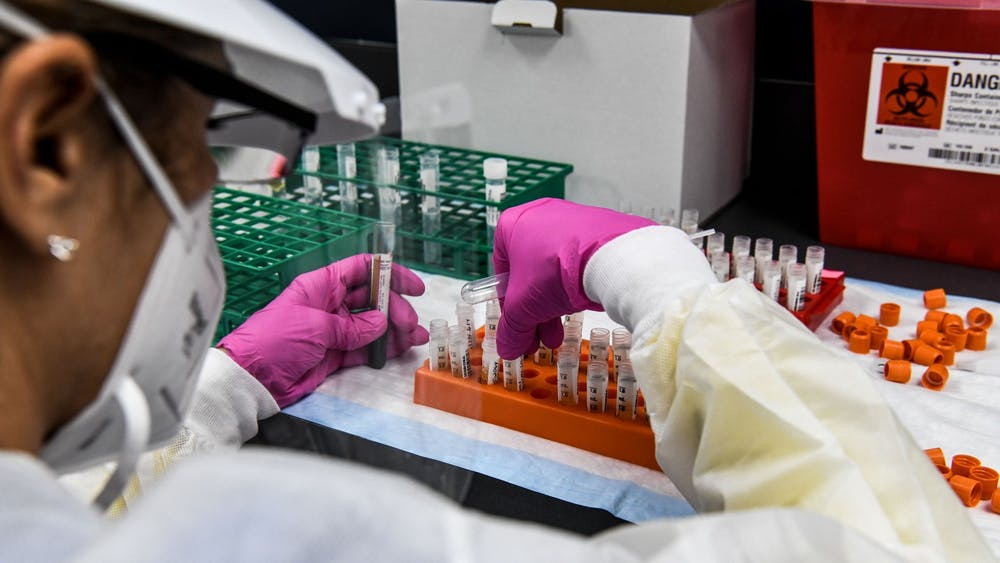 A lab technician sorts blood samples inside a lab for a COVID-19 vaccine study at the Research Centers of America on Aug. 13 in Hollywood, Florida.