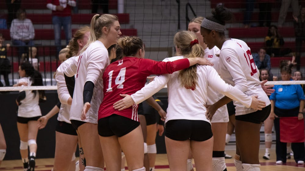 IU volleyball players confer between points during the fifth set against Iowa on Oct. 26 at Wilkinson Hall. IU will play at No. 8 Penn State on Friday followed by a matchup at Rutgers on Saturday.